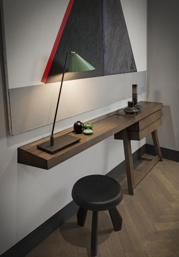 Uma lampâda e a cadeira transformam o corredor em um espaço de leitura ou trabalho